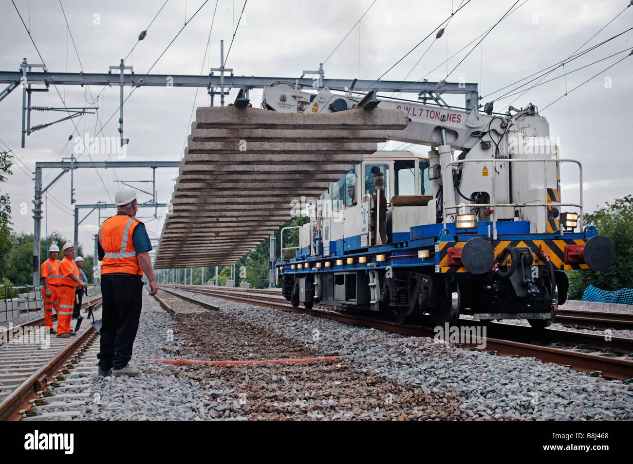 Self-propelled twin-jib railway crane lifting heavy section of redundant track panel during a track replacement - Stock Image