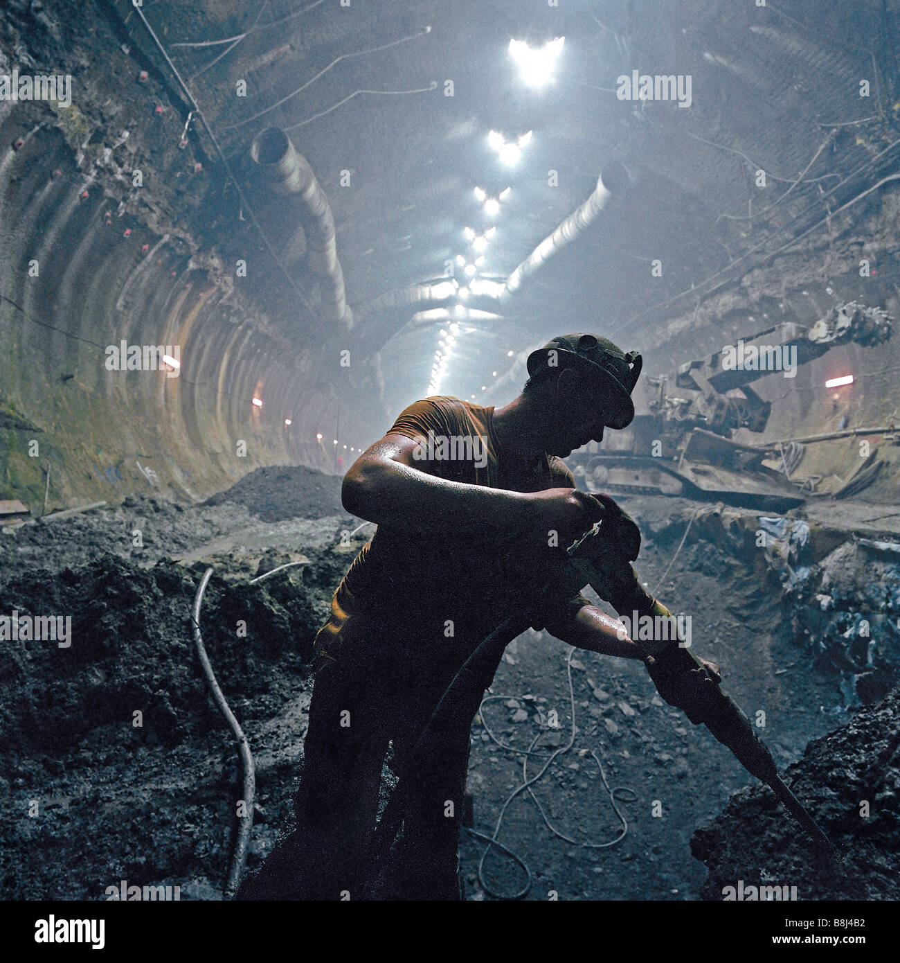 Channel Tunnel contractor trimming excavation with hydraulic air spade in the huge UK Crossover cavern - Stock Image