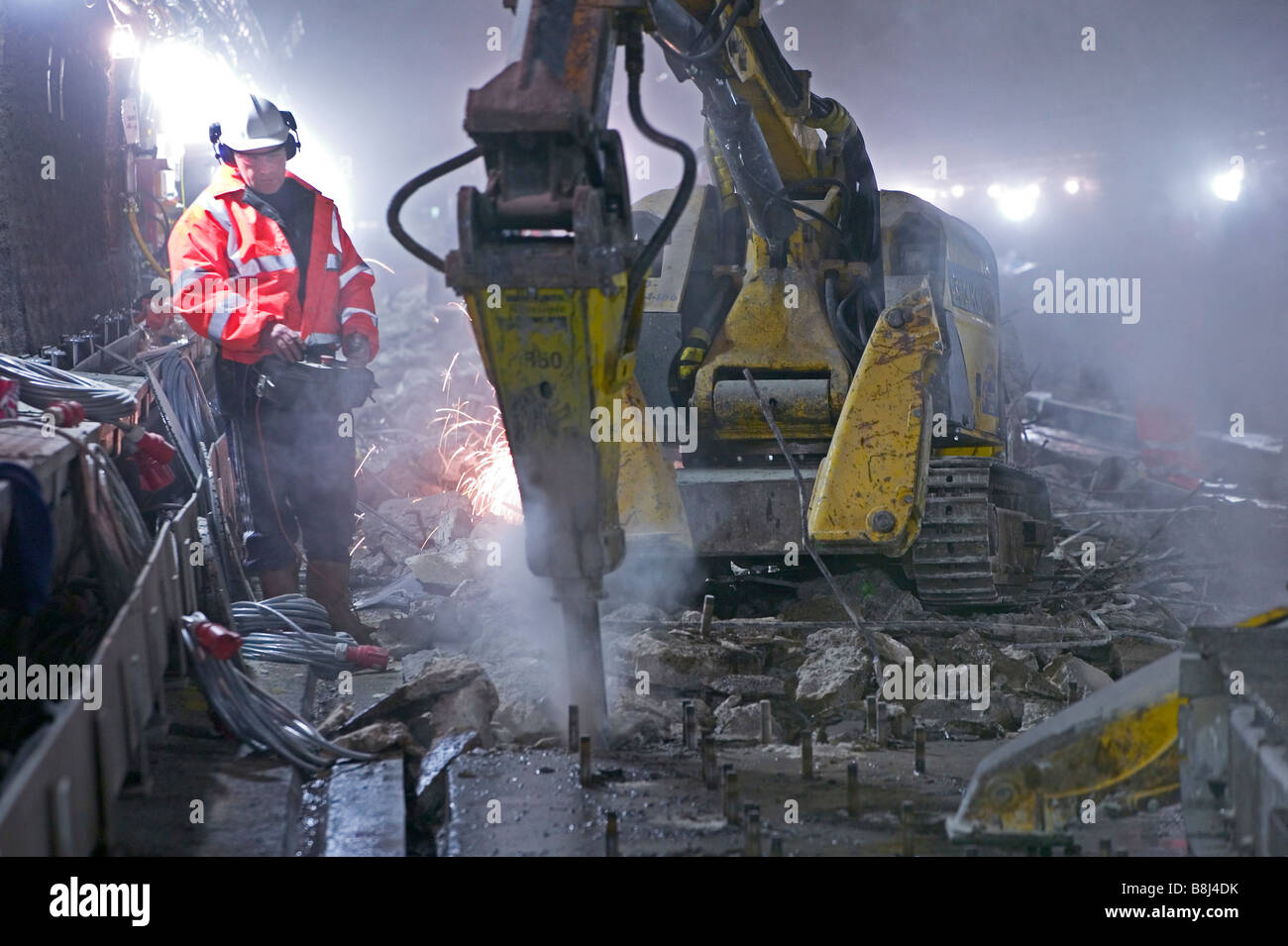 Operative using remote controlled concrete breaker excavating worn-out deck under the tracks during rail tunnel - Stock Image