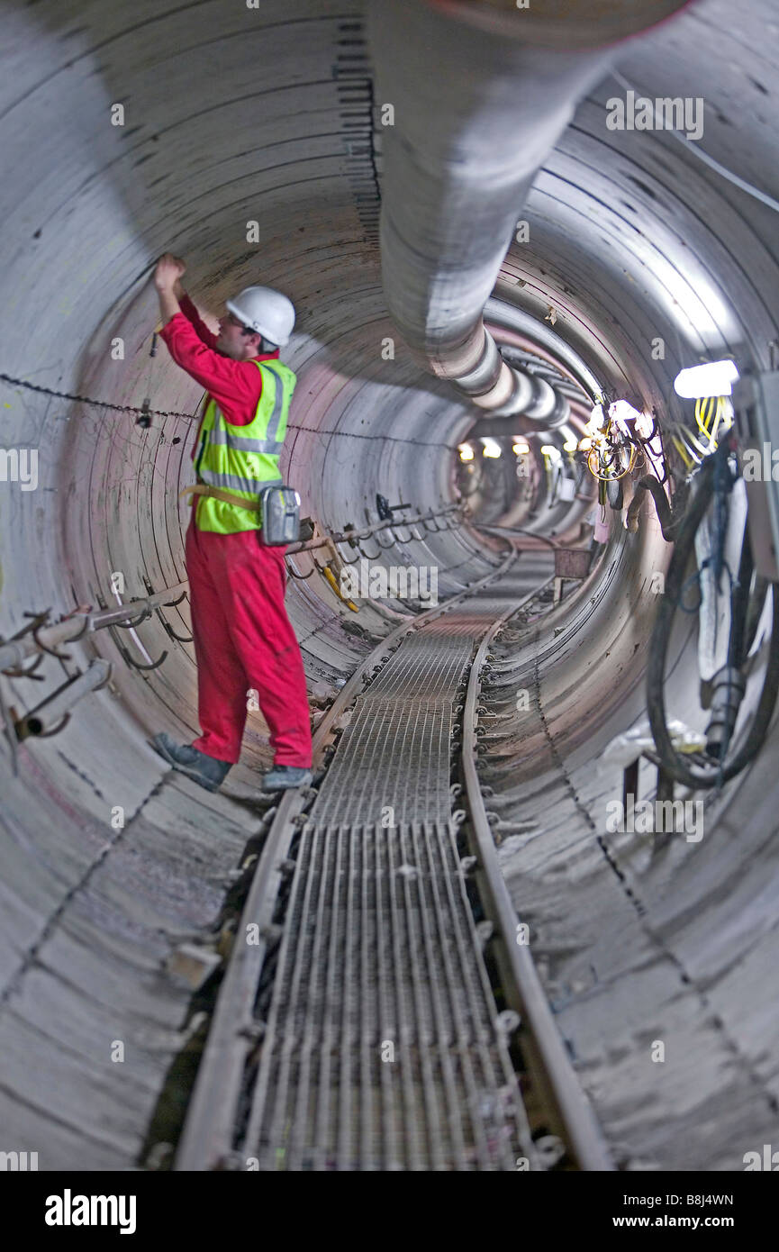 Engineer inspects concrete segments installed in this winding power cable tunnel, excavated by a tunnel boring machine. - Stock Image