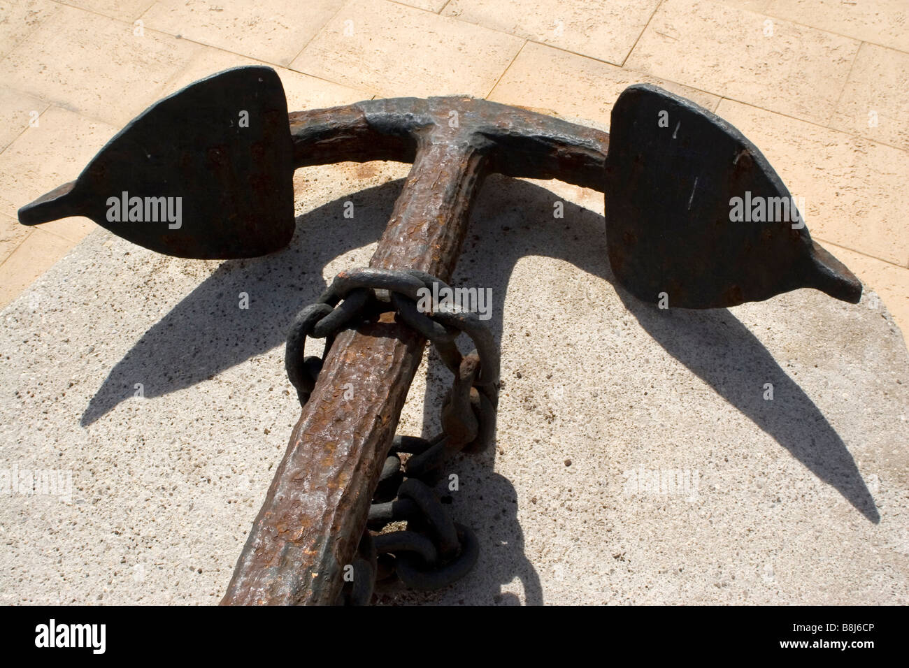 An anchor is displayed close to a port on the island of Mallorca (Majorca). - Stock Image