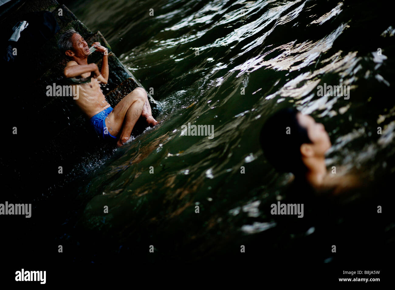 A man scrubs himself after swimming in the Pearl River in Guangzhou, China. - Stock Image