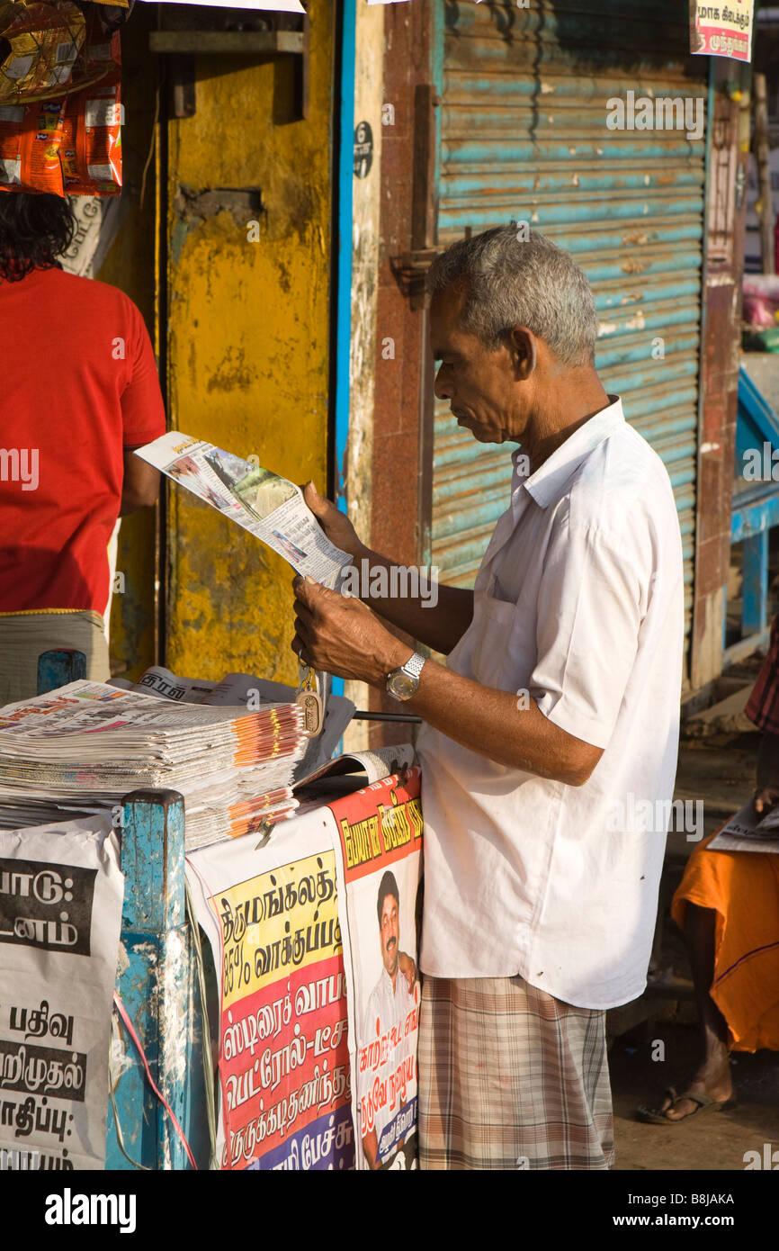 India Tamil Nadu Kumbakonam Man browsing Tamil language newspaper at