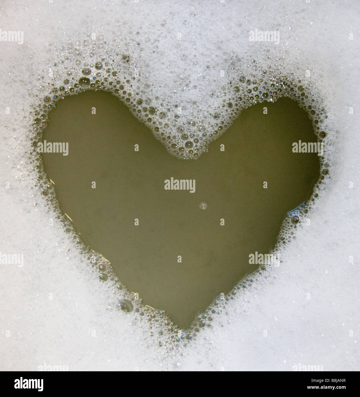 Heart shape in dishwater soapsuds - Stock Image
