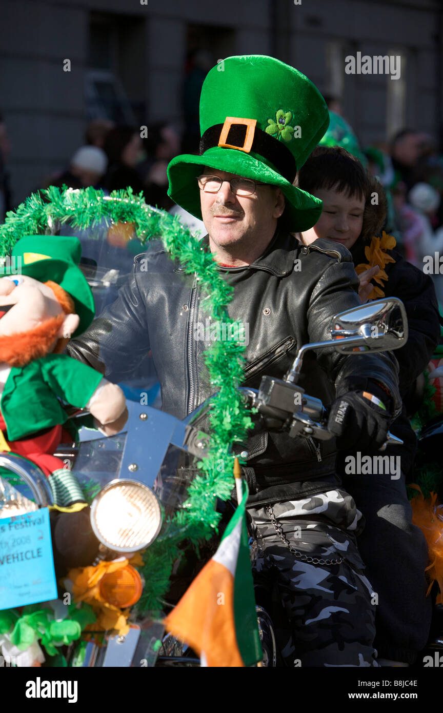 A biker participant rides past the crowd in the St Patricks Day Parade in Dublin Ireland - Stock Image