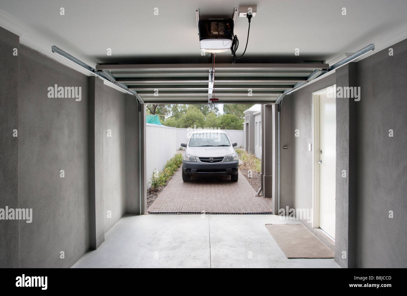 A Car Driving Into A Garage With An Automatic Garage Door