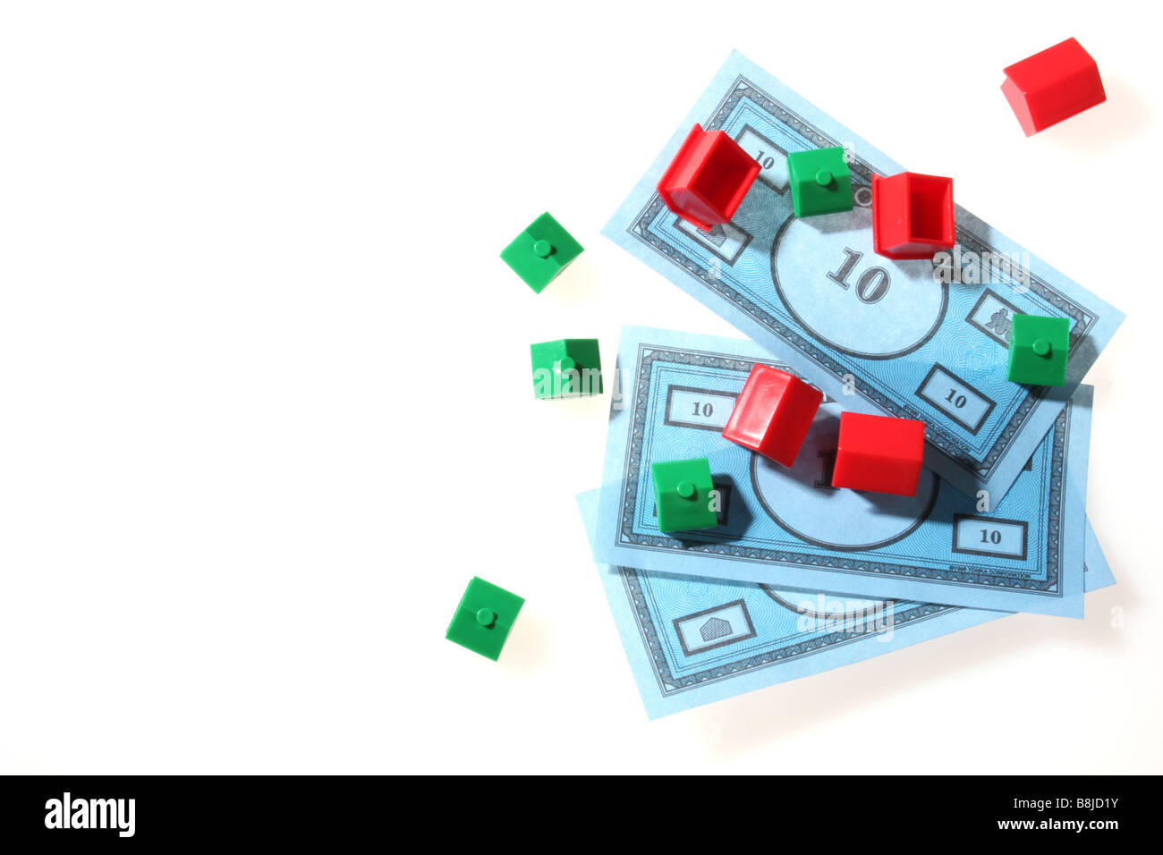 Monopoly houses and hotels on top of toy bank notes - Stock Image