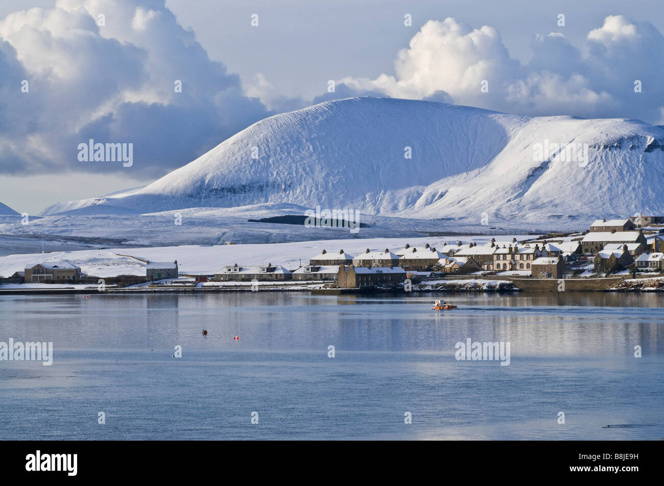 dh Harbour STROMNESS ORKNEY Fishingboat leaving harbour winter snow white hills landscape scenery Stock Photo