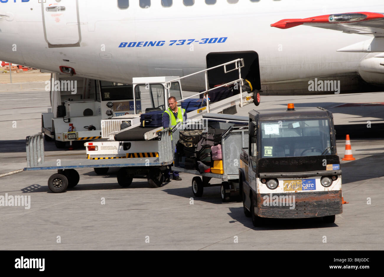 Baggage handler unloading luggage from a Boeing 737 jet aircraft at Malaga International Airport southern Spain - Stock Image