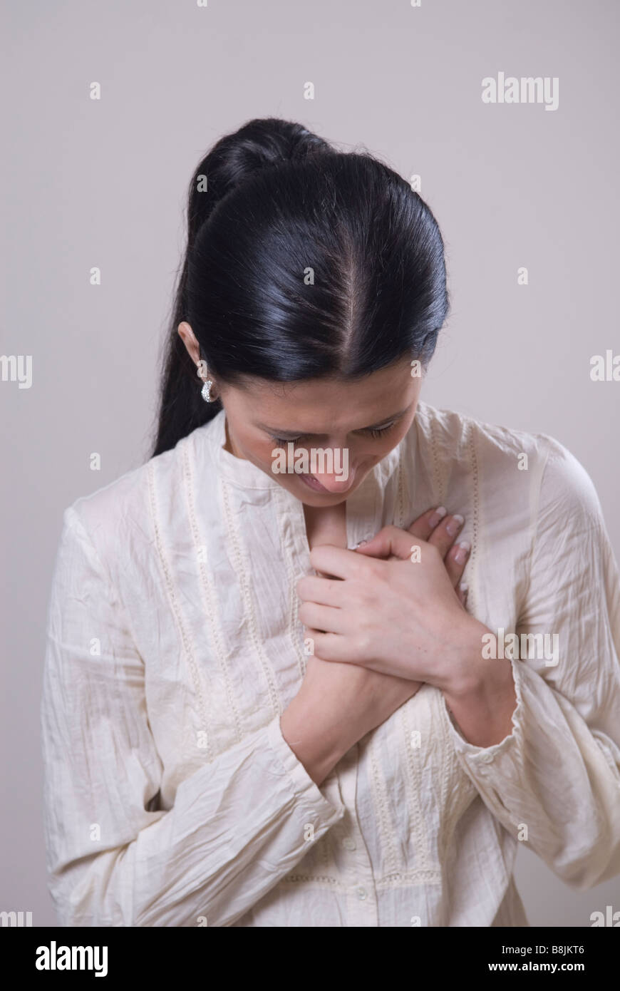 Young woman hands over heart - Stock Image