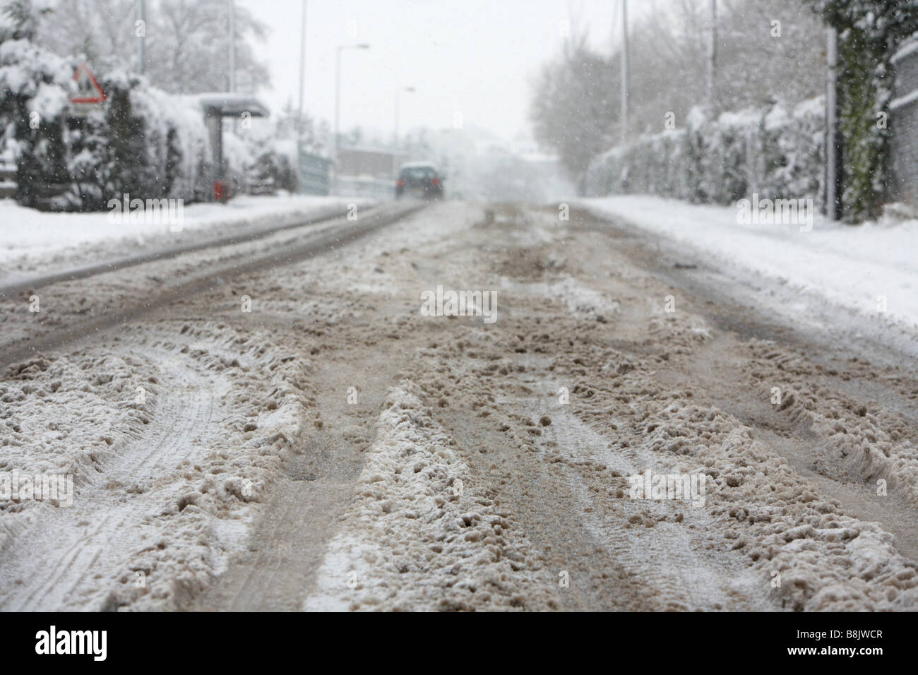 gritted salted lying snow turning to slush with tire tyre tracks going uphill in the middle of the road - Stock Image