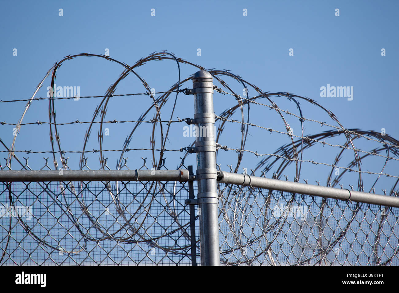 Security fence surrounding a detention center - Stock Image