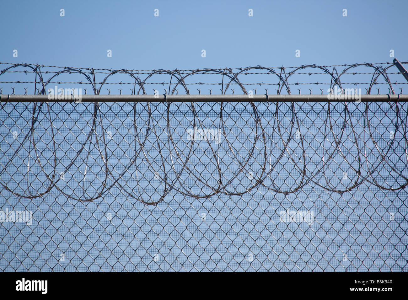 Barbed wire security fence surrounding a detention center - Stock Image