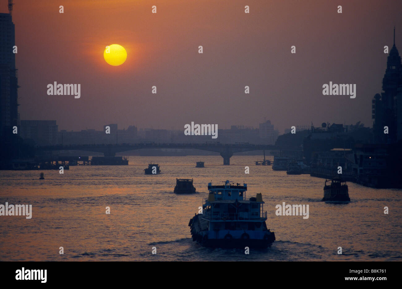 Pearl River Estuary River traffic Boats Bridge Buildings Large orange sun in sky sunset GUANGZHOU CHINA - Stock Image