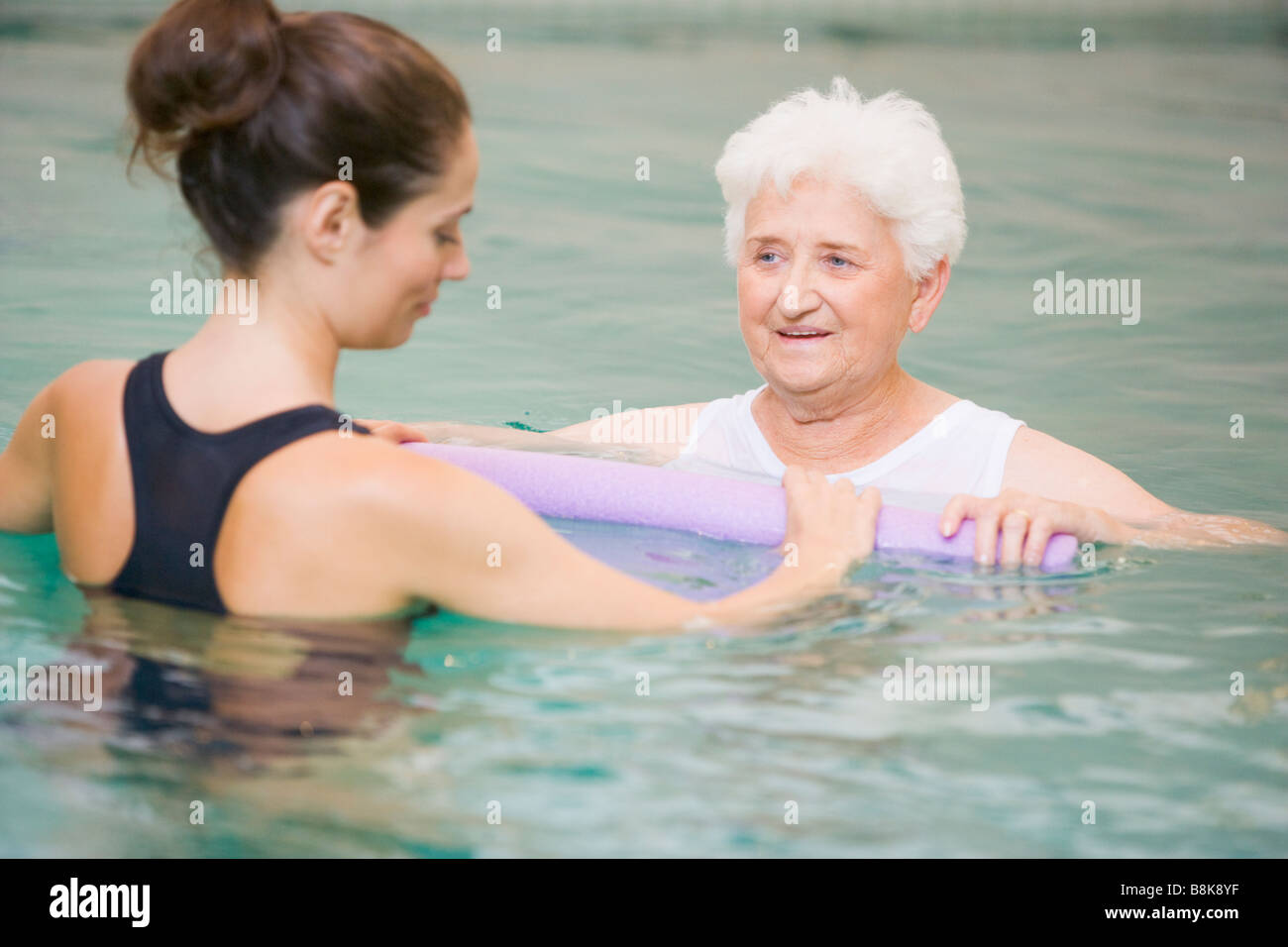 Instructor And Elderly Patient Undergoing Water Therapy - Stock Image