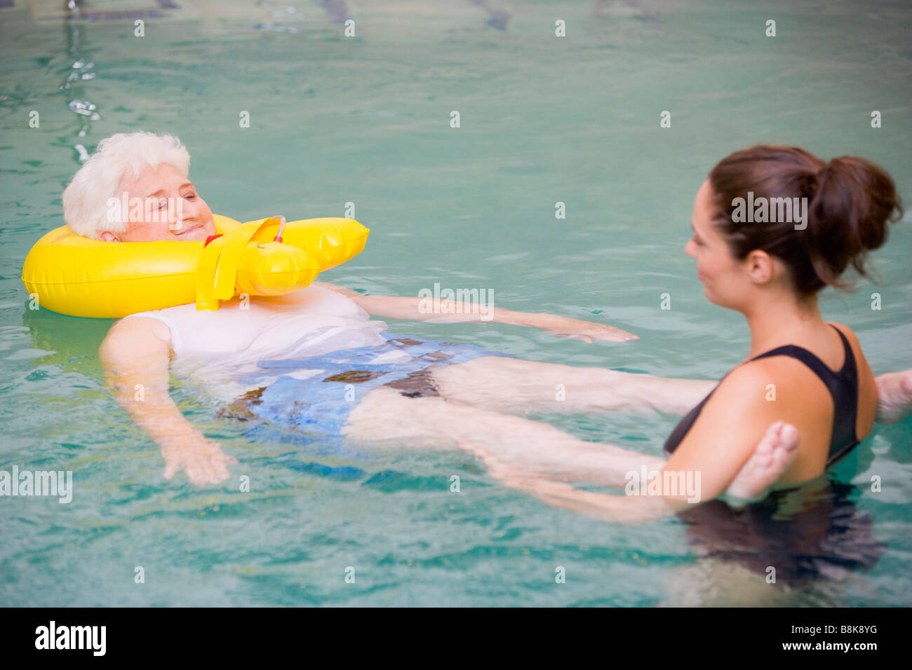 Instructor And Elderly Patient Undergoing Water Therapy Stock Photo