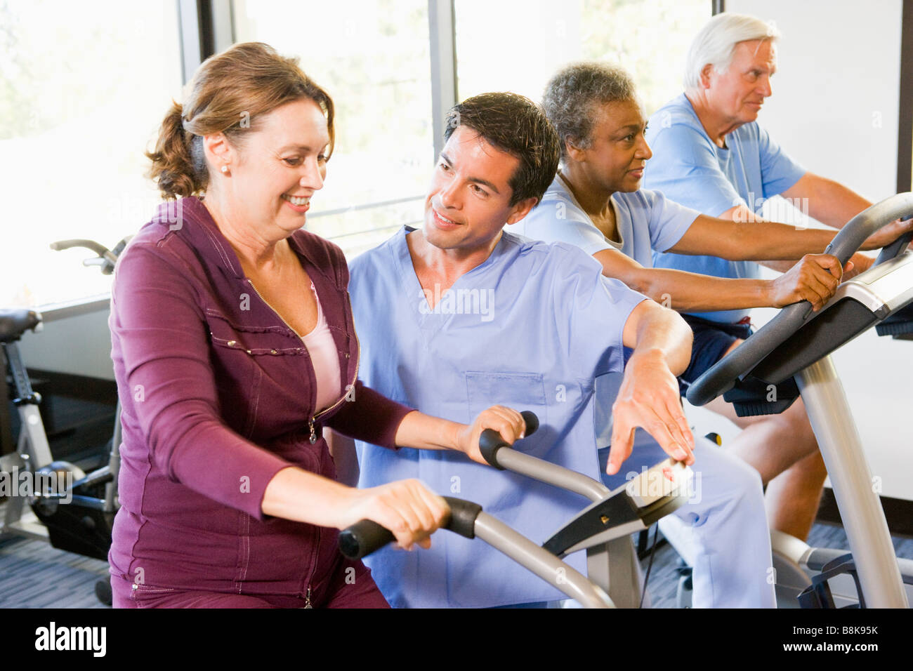Nurse With Patient In Rehabilitation Using Exercise Machine - Stock Image