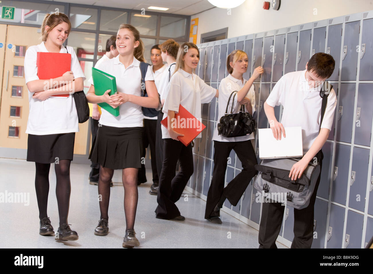 Secondary school students in a school hallway - Stock Image