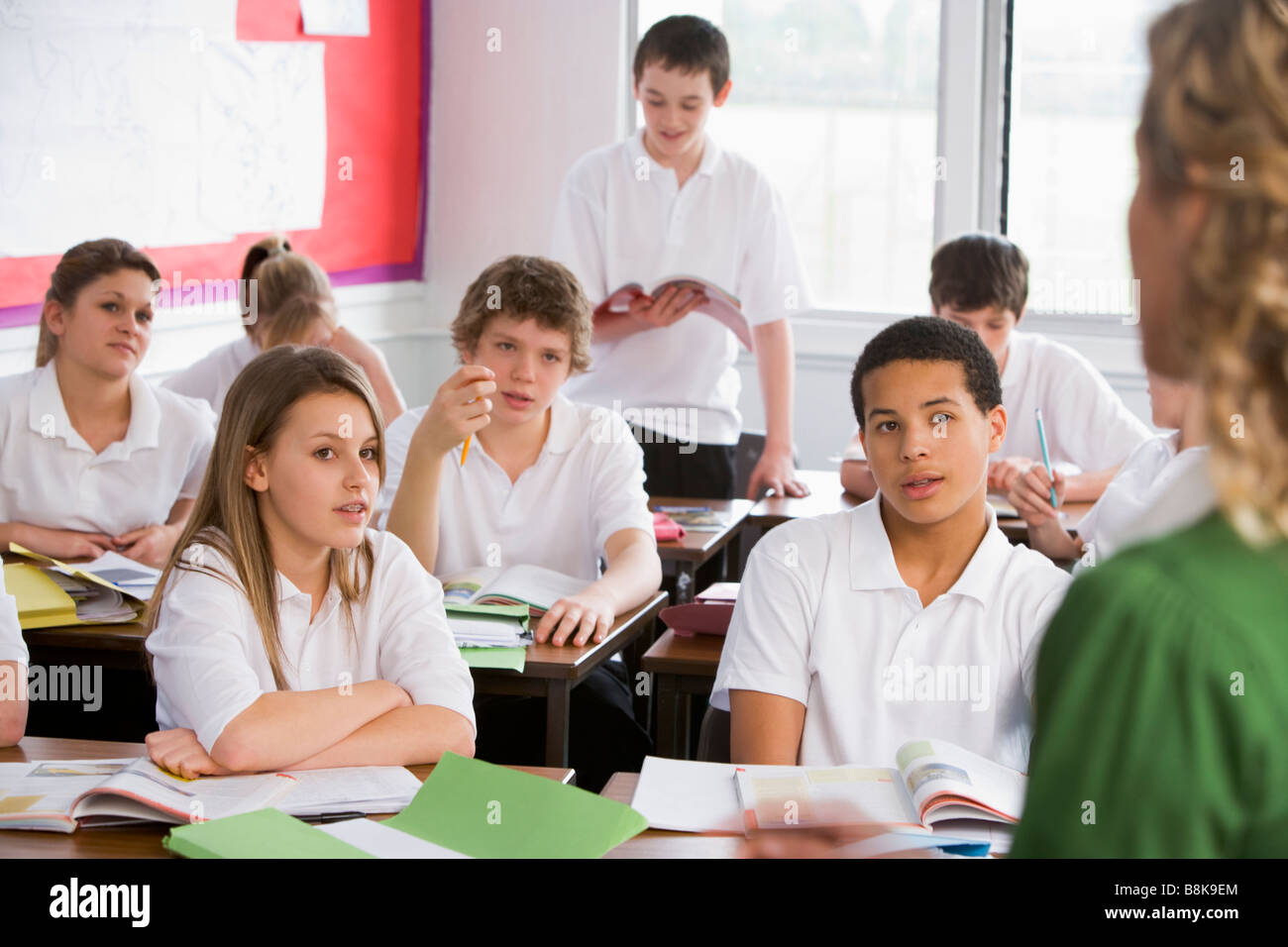 Secondary school student reading out loud in classroom - Stock Image