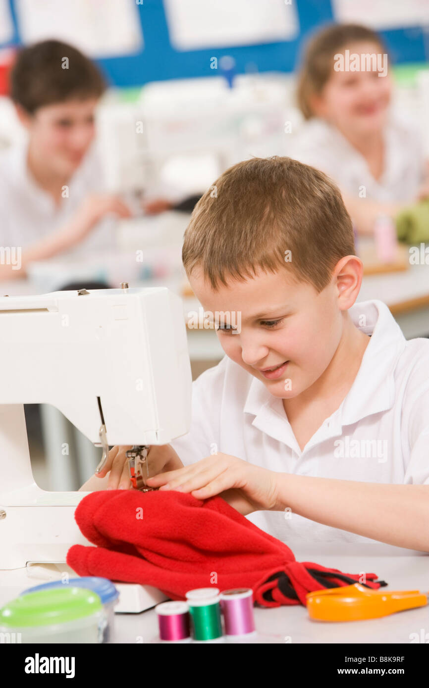 Male student using sewing machine - Stock Image