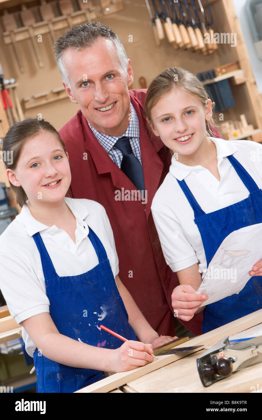 Female students reviewing woodworking plans with teacher - Stock Image