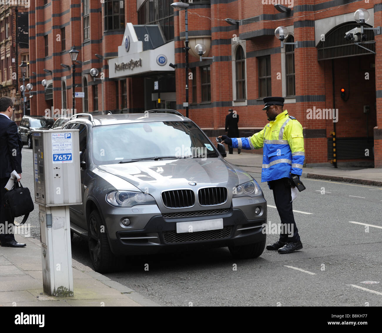 Traffic Warden Civil Enforcement Officer photographing the tax disc of a car in Birmingham West Midlands after issueing - Stock Image