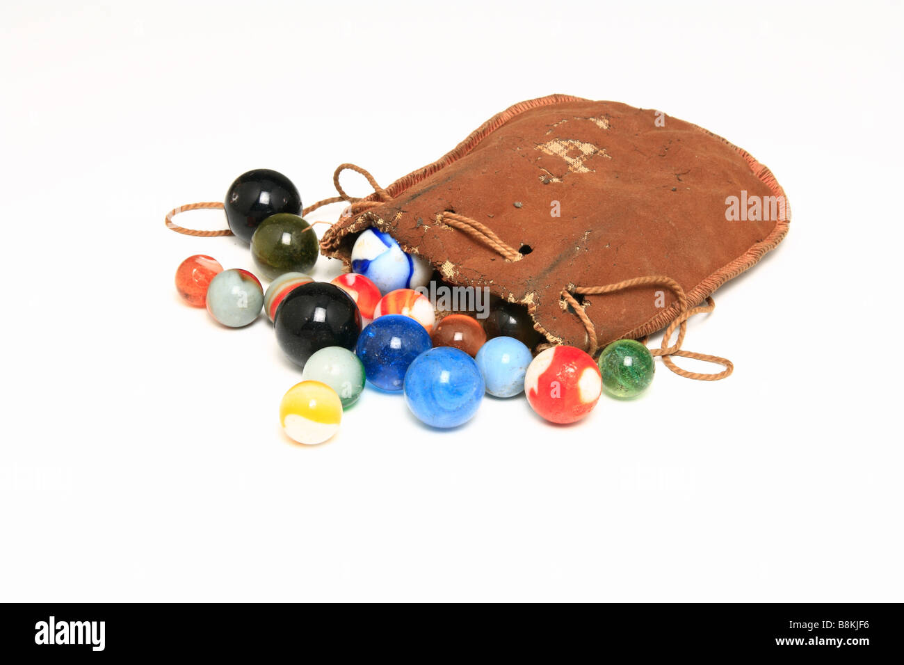 Collection of marbles spilt from a weathered leather pouch. - Stock Image