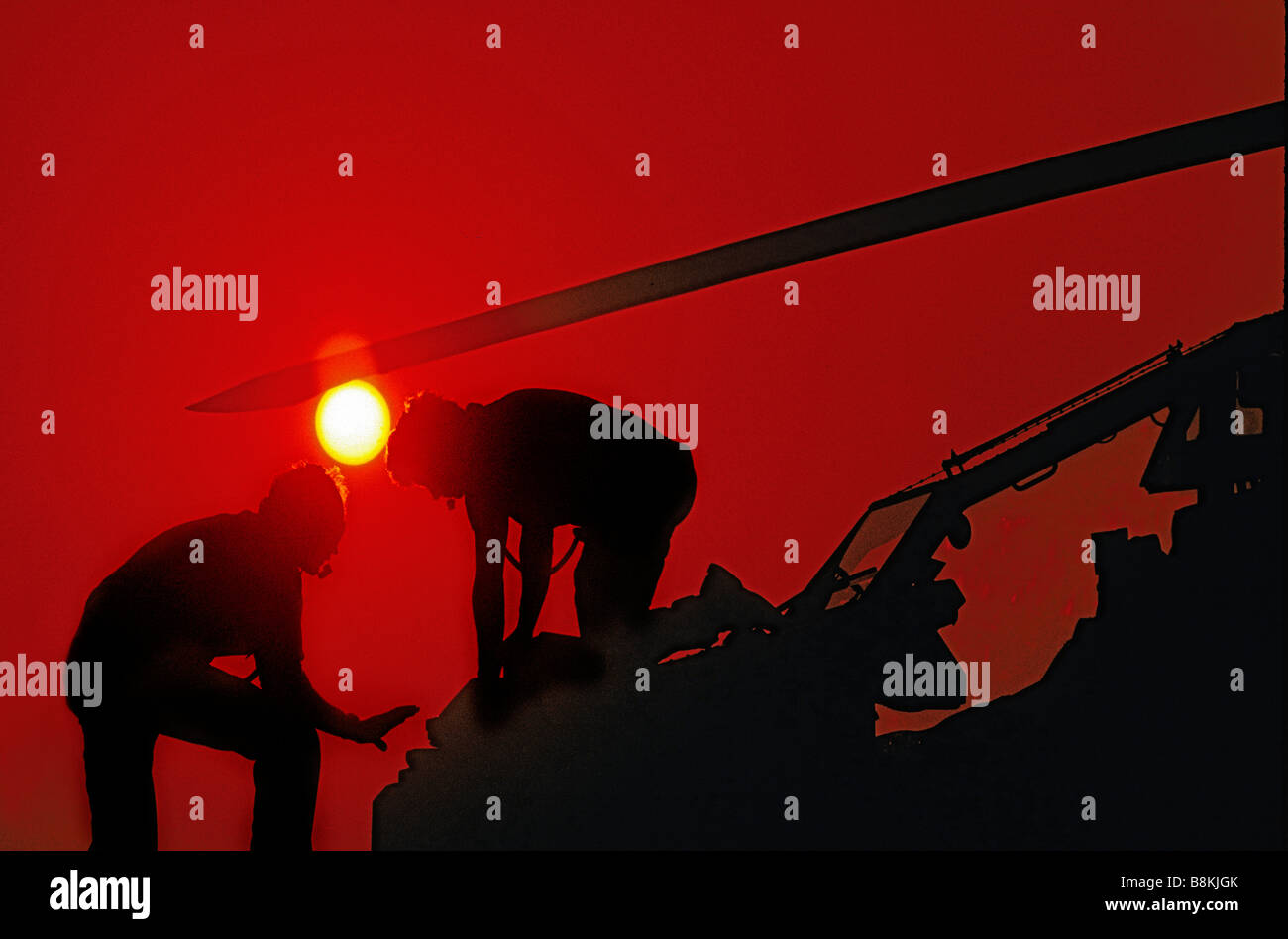 Silhouette with sun of two aerospace technicians working on nose of helicopter. - Stock Image