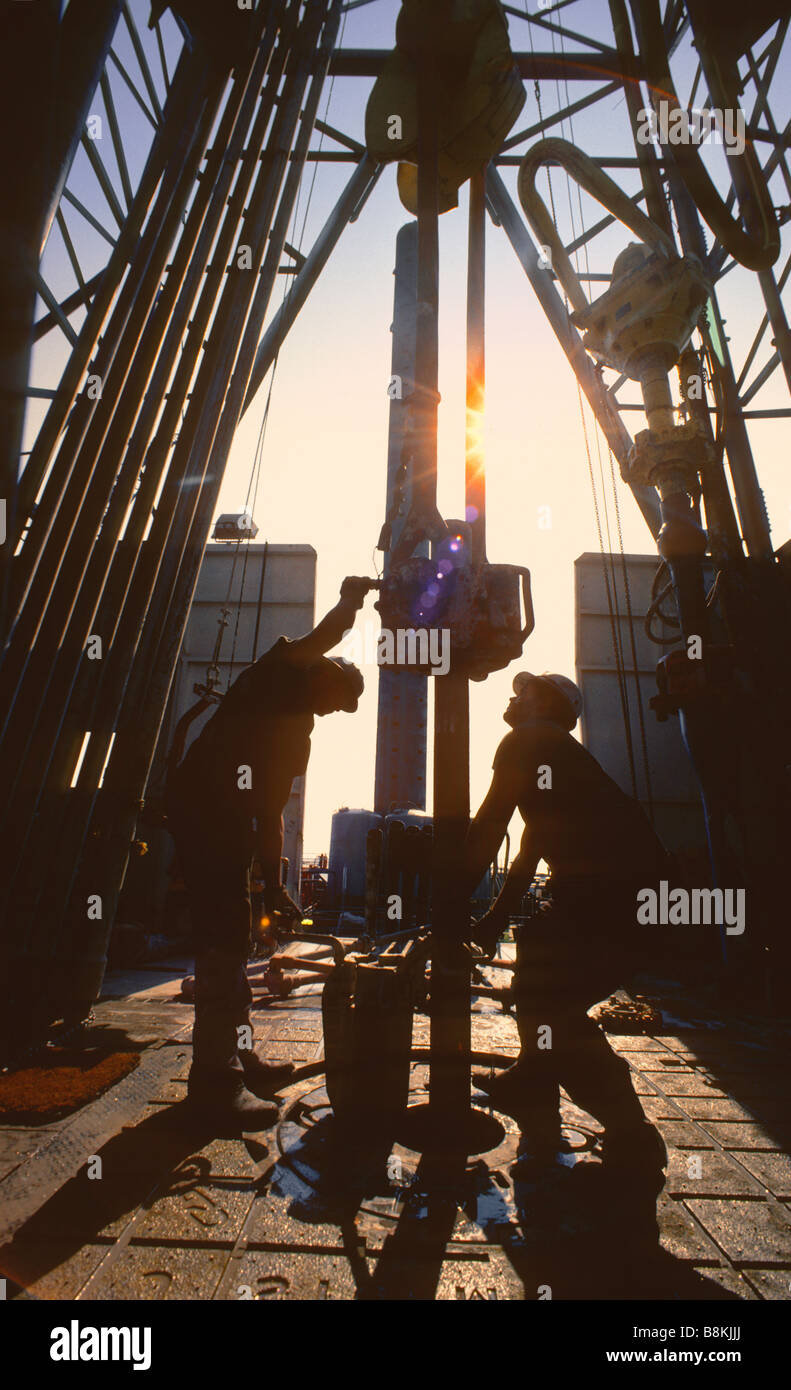 Two workers with drill bit, drill collar and piping on offshore oil rig, Gulf of Mexico, USA. - Stock Image
