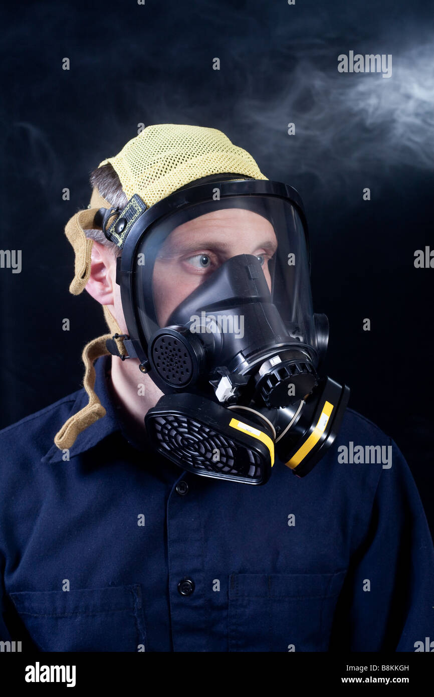 man wearing respirator or gas mask while exposed to toxic gas or smoke - Stock Image