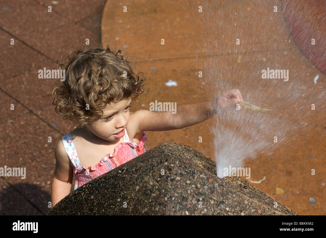 Child Plays with a Squirting Water Fountain in an Urban Playground in New York, USA - Stock Image