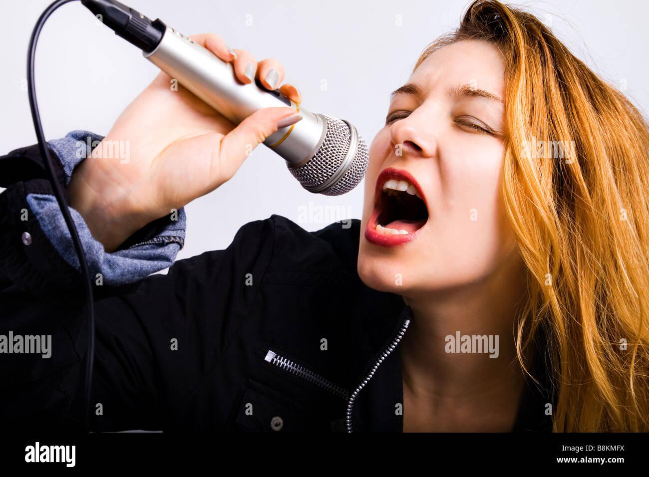 Young female karaoke singer singing music at microphone - Stock Image