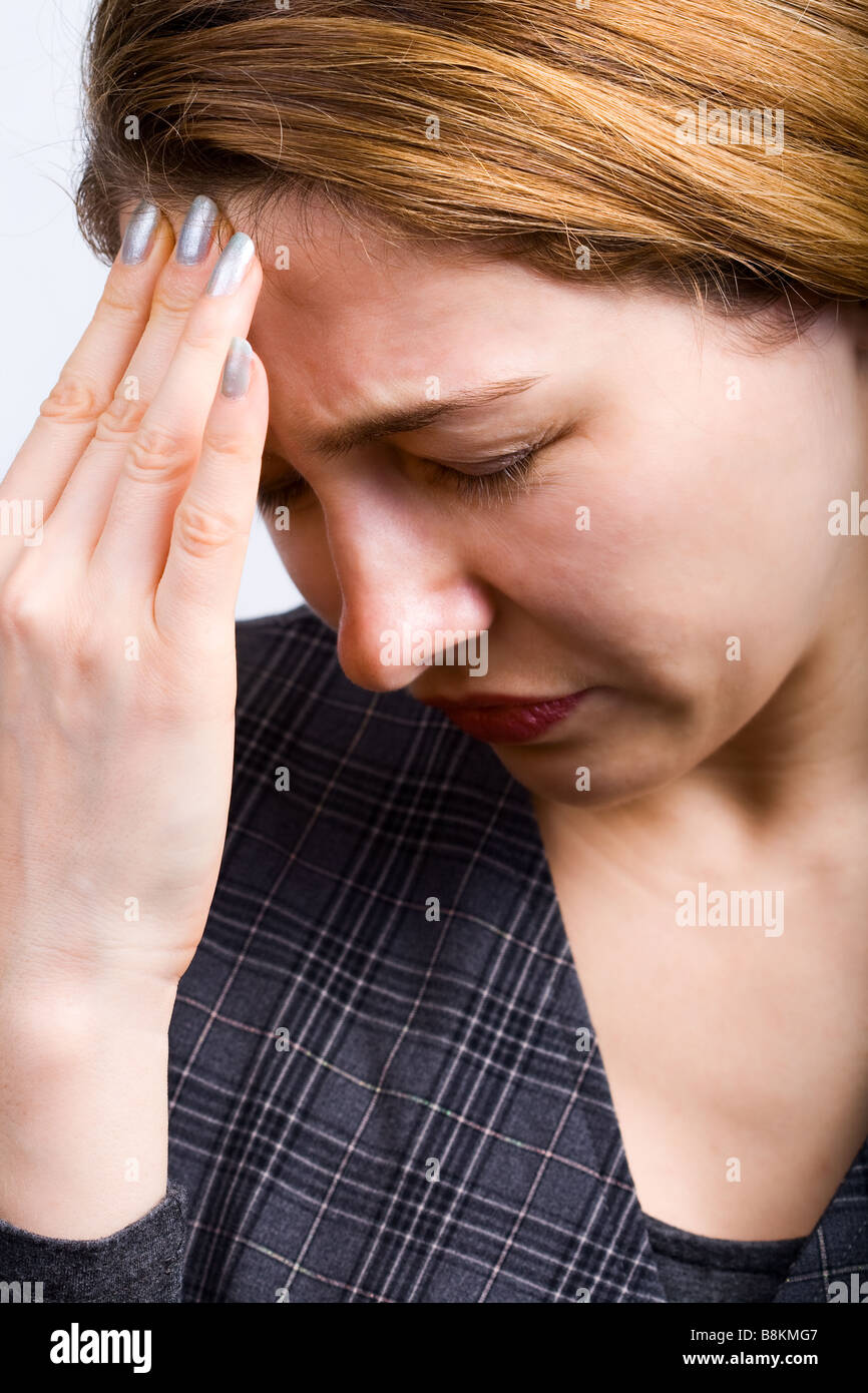 Portrait of businesswoman with big headache - Stock Image