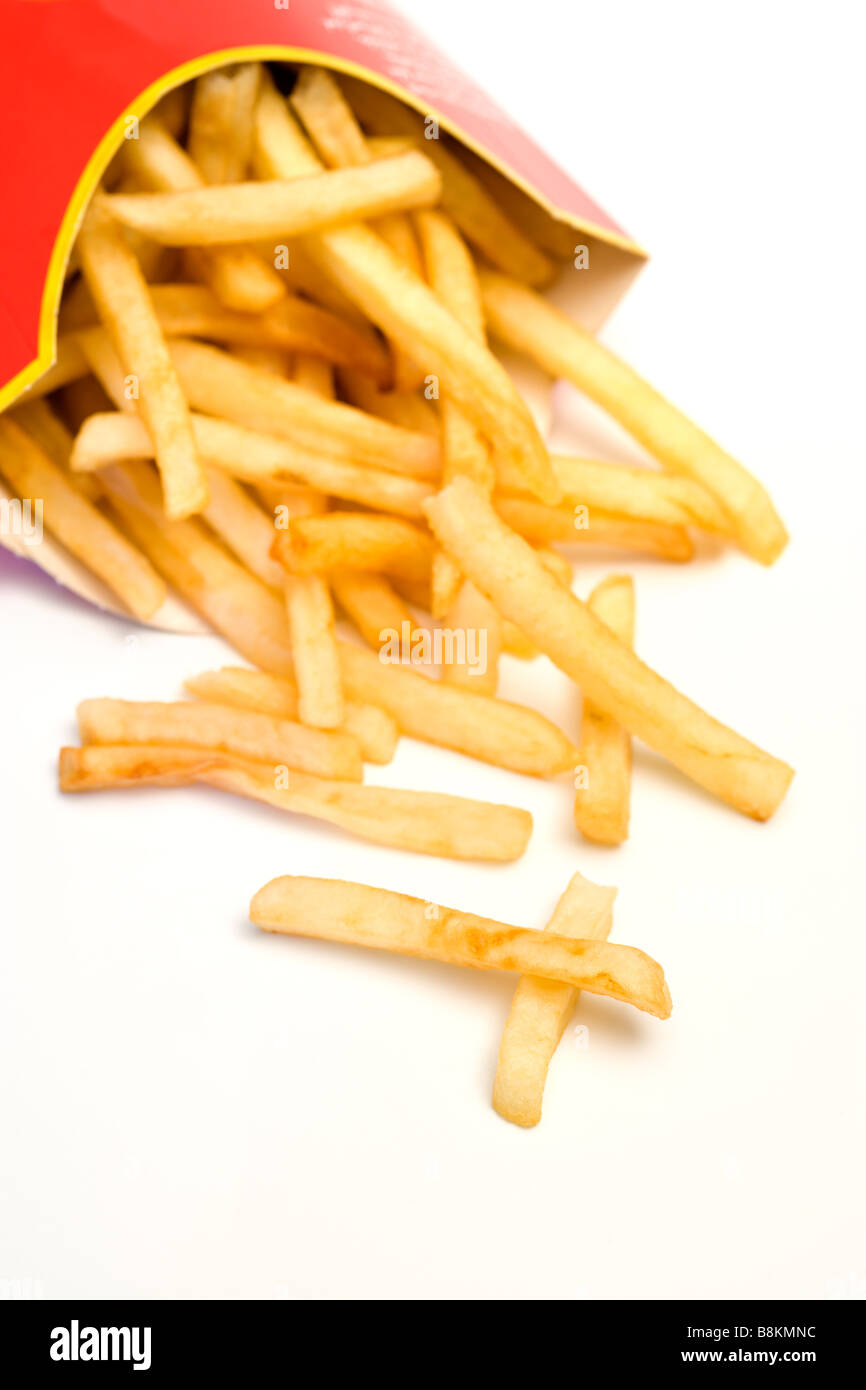Unhealthy fast food. French fries falling from tilted cardboard box, two pieces resembling a cross, white background - Stock Image