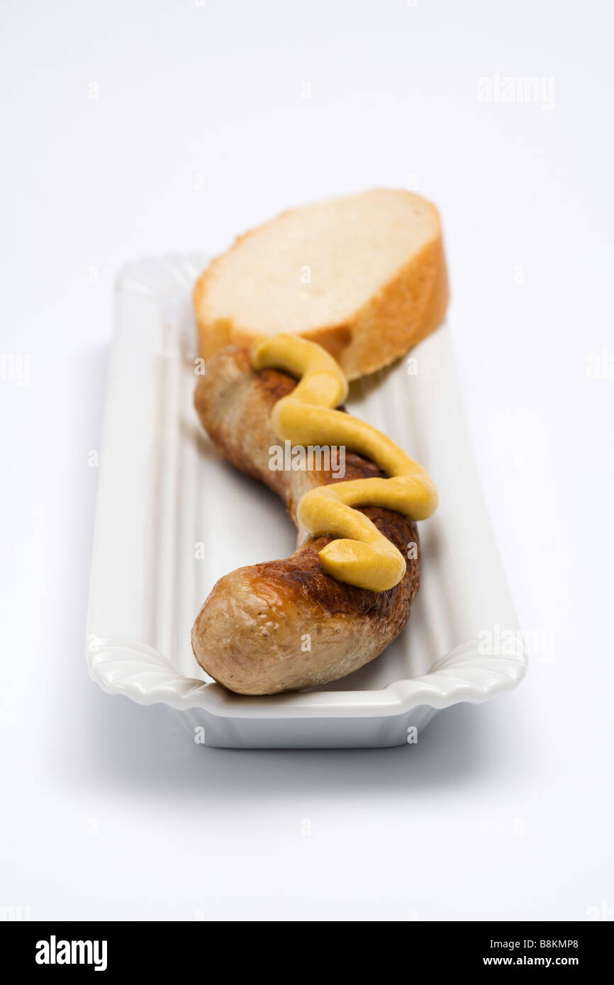 german Thuringer Bratwurst with mustard and slice of bread on serving dish, placed on white background, frontal Stock Photo