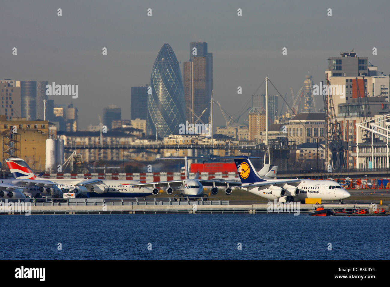 Overview on London City Airport with London's skyscrapers in background - Stock Image