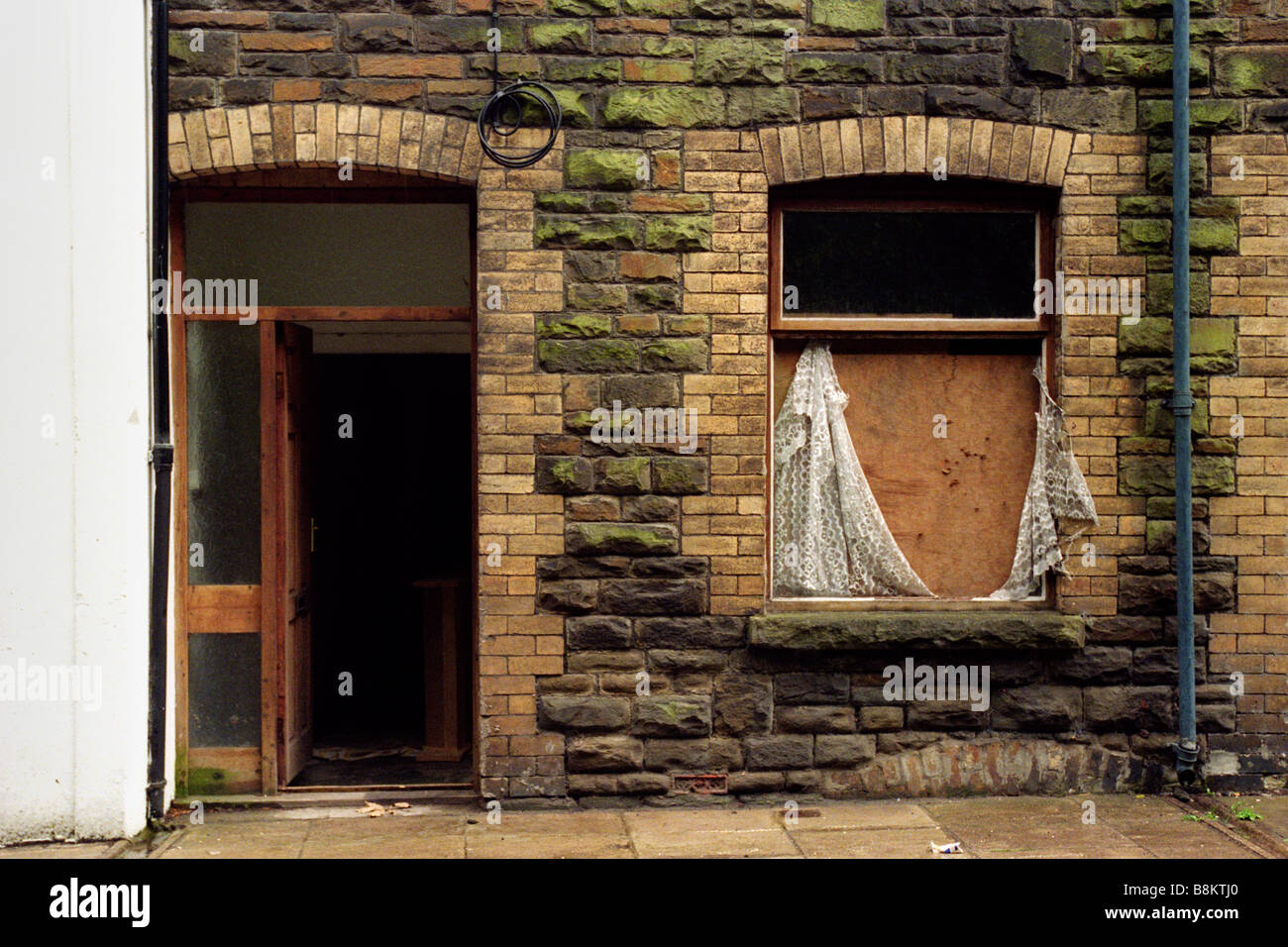 Derelict house with boarded up window Six Bells Blaenau Gwent Wales UK - Stock Image