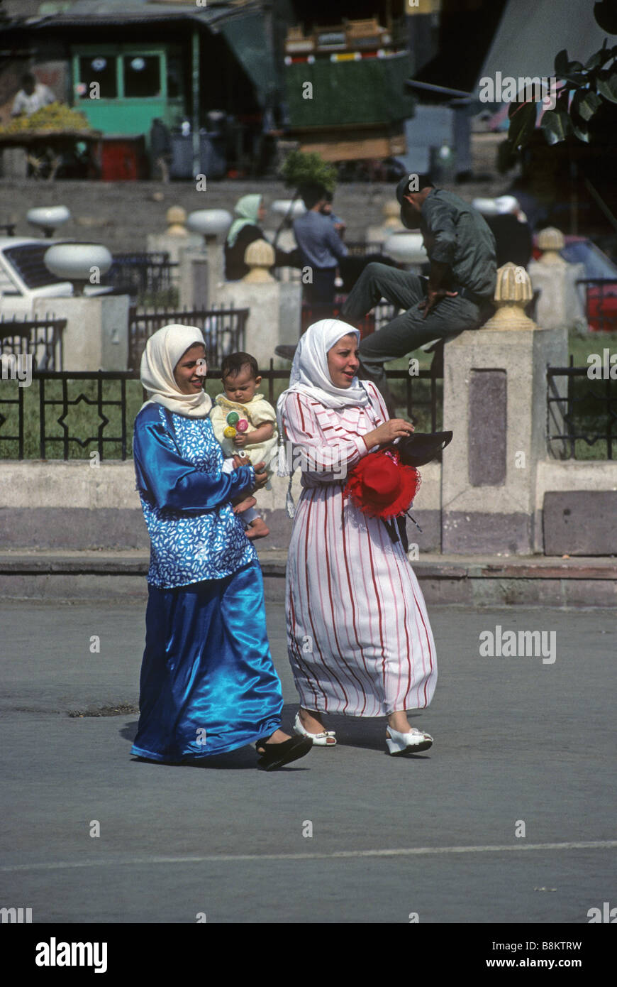 Two Egyptian women in hijabs carrying a baby while walking through Khan el Khalili bazaar Cairo Africa Known as - Stock Image