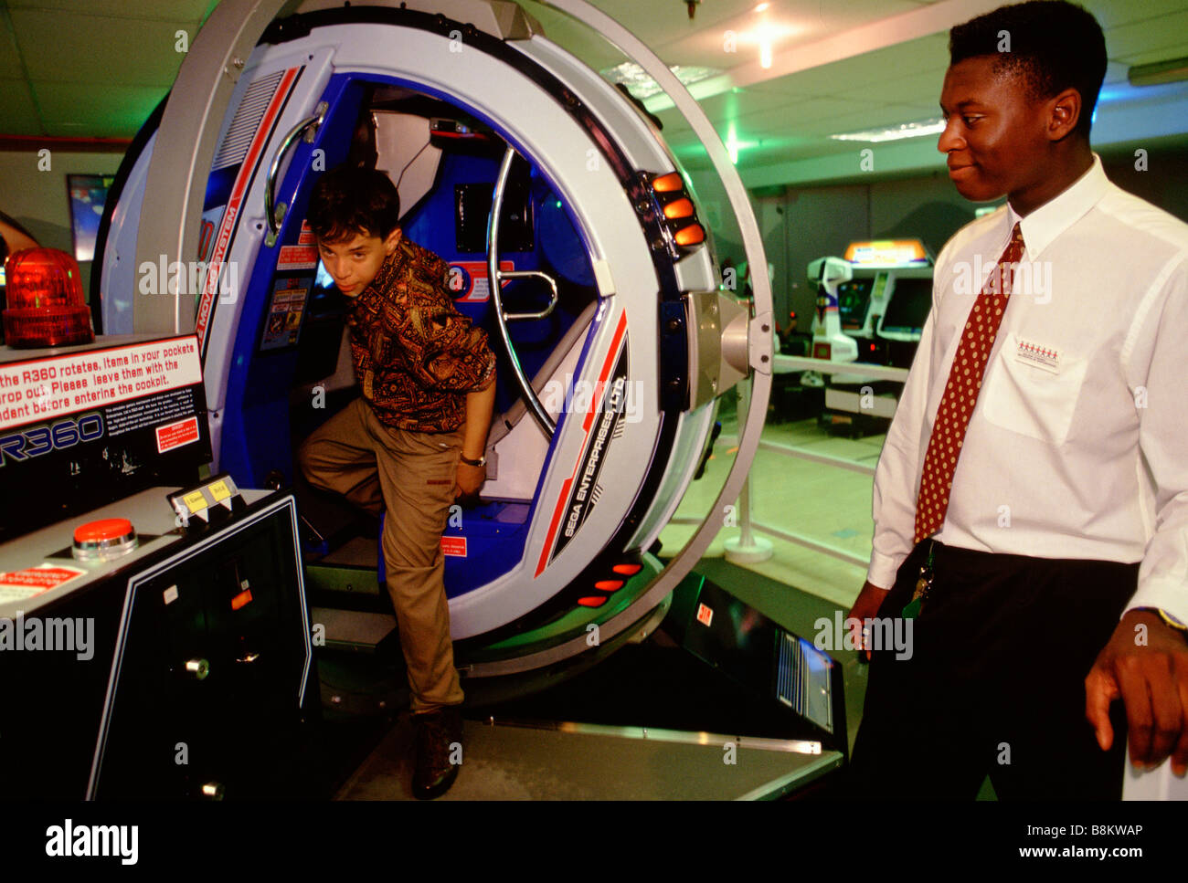 Hamley's Toy Shop London UK A young boy get out of the R360 servo based game on Sega games floor. - Stock Image