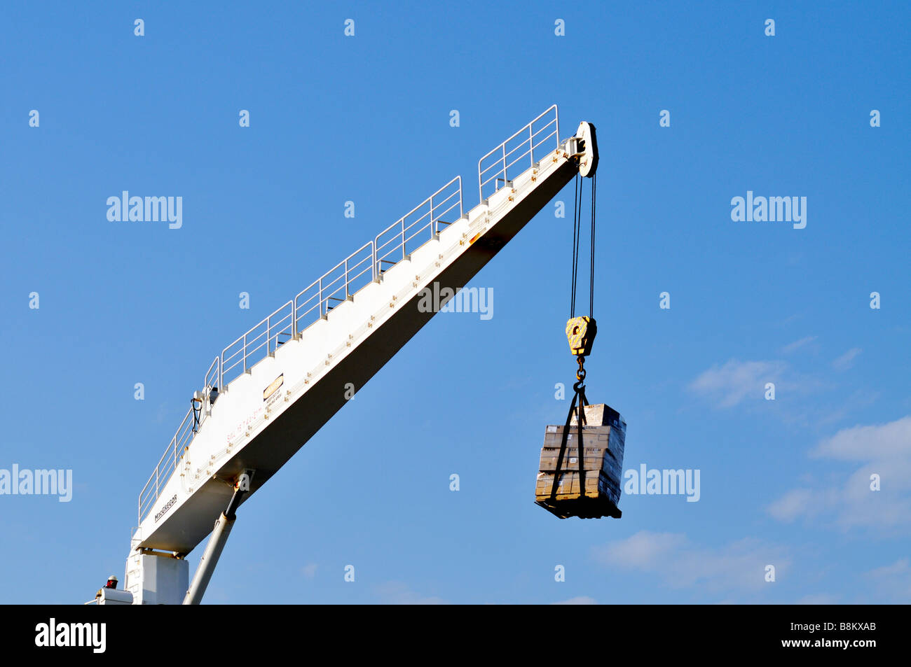 Crane hoisting a heavy pallet of ship's supplies against a [clear deep blue sky]. - Stock Image
