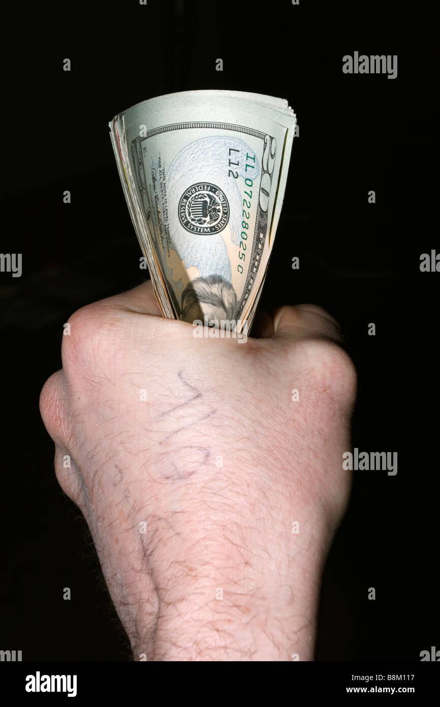 Male left hand clenching small bundle of USD twenty dollar bills, with the word OIL written on back of hand. - Stock Image