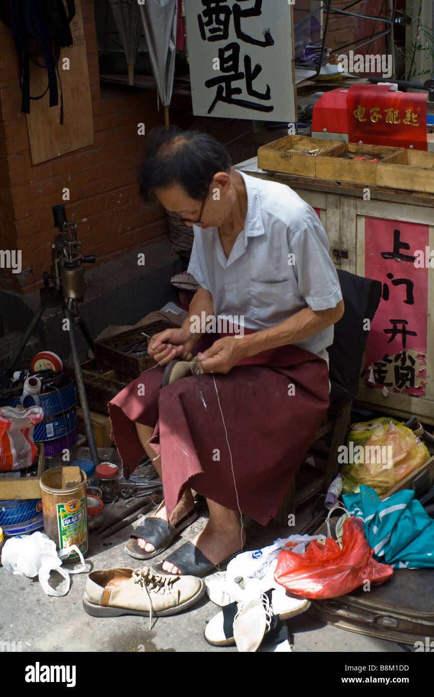 A shoemaker in the traditional chinese quarter of Shanghai, China. - Stock Image
