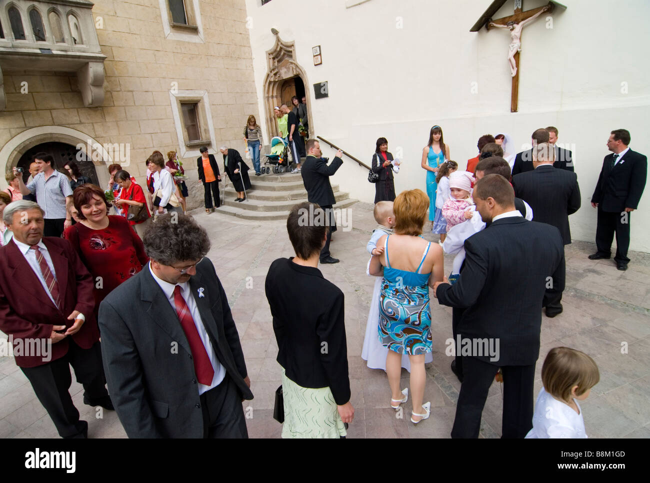 Newlyweds in front of the church of the Holy Cross and the the Matthias House  in the castle complex of Banska Bystrica - Stock Image