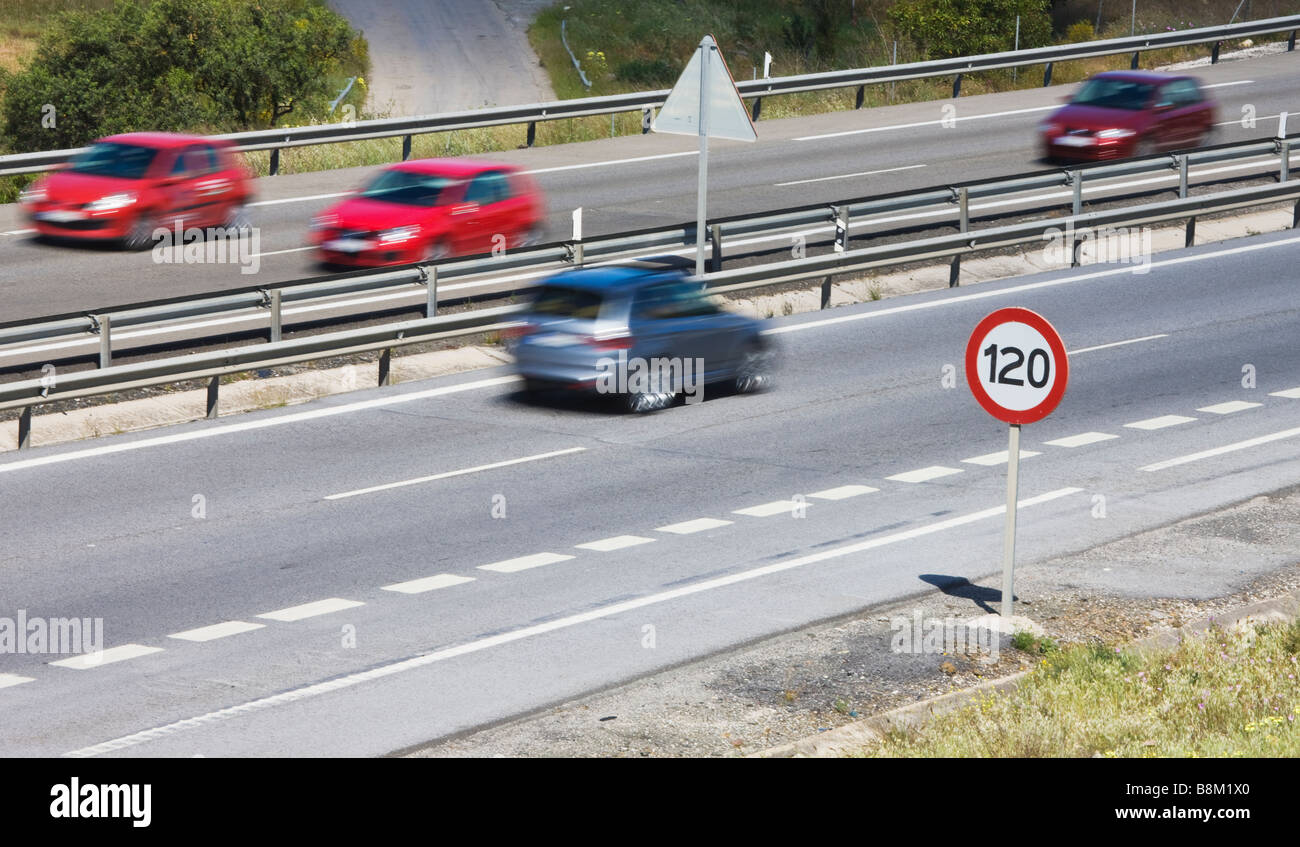Cars passing 120 kilometer per hour speed limit sign on motorway in Spain - Stock Image