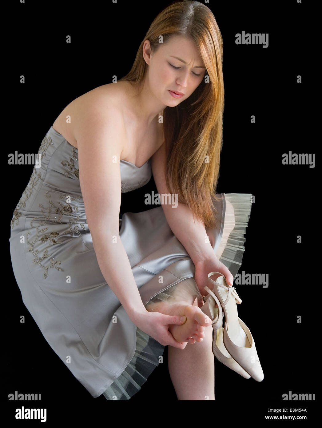 Young woman in a party dress. She has taken her shoes off and is massaging her sore feet. - Stock Image