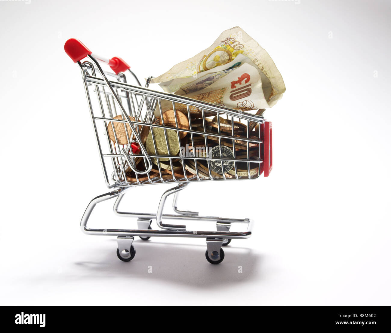 cash in a miniature shopping trolley - Stock Image