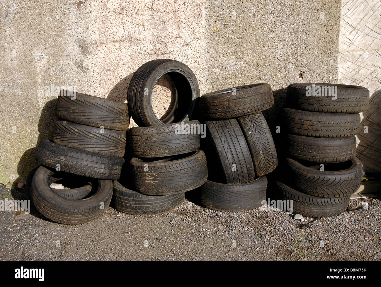 Tyres stacked up against a garage wall. - Stock Image