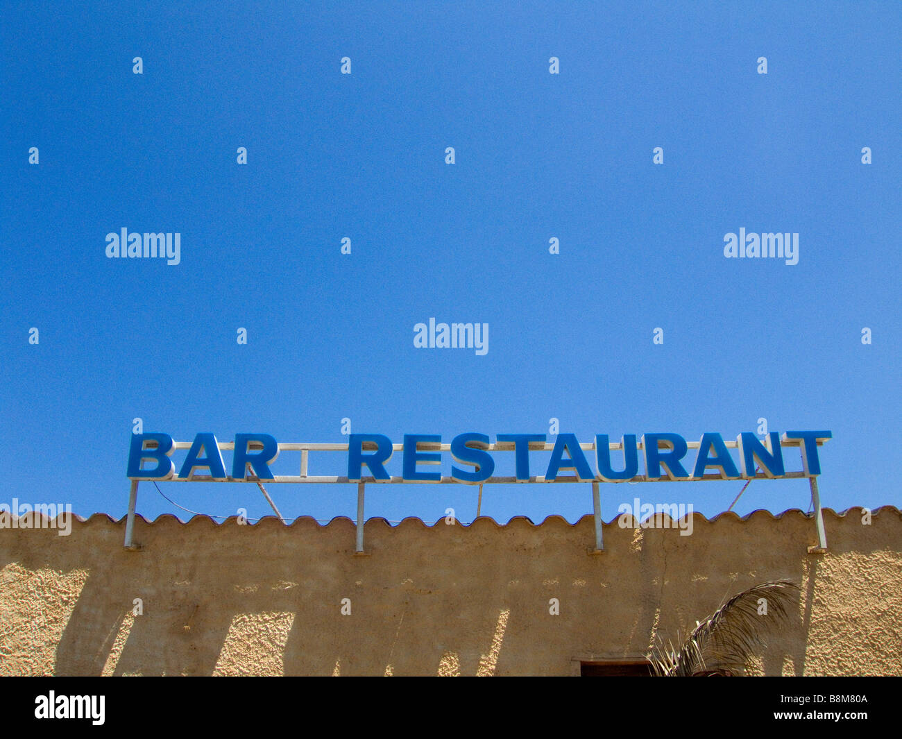 A Bar Restaurant sign against a blue sky - Stock Image