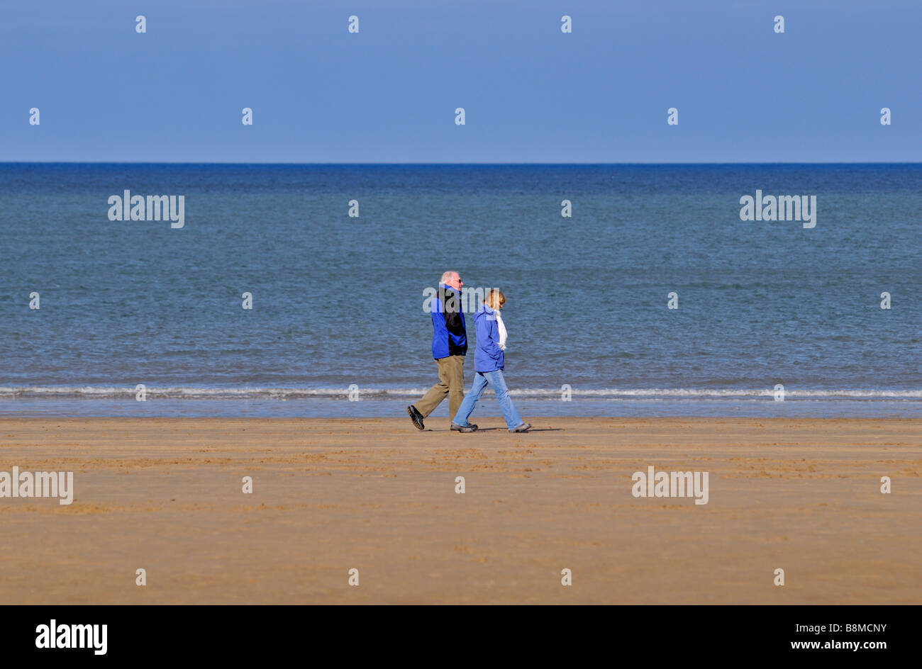 Couple strolling on Colwyn Bay sands, Wales, United Kingdom - Stock Image