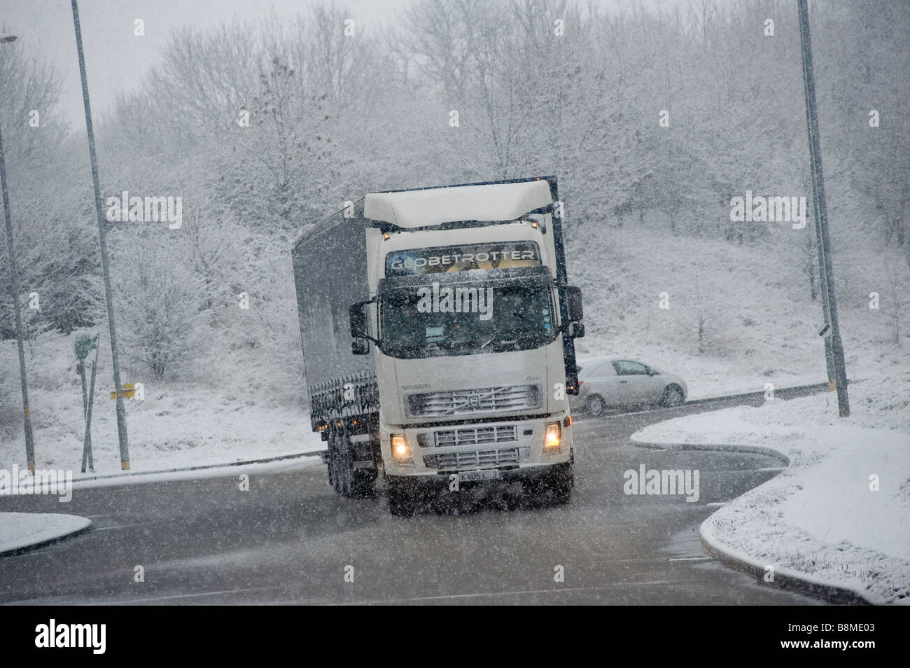 Volvo FH12 HGV lorry driving slowly on a snowy road in winter in England - Stock Image